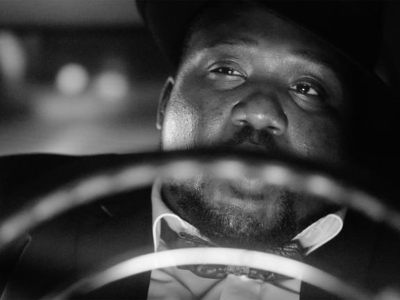 Frontal close up black and white photograph of a man driving a car