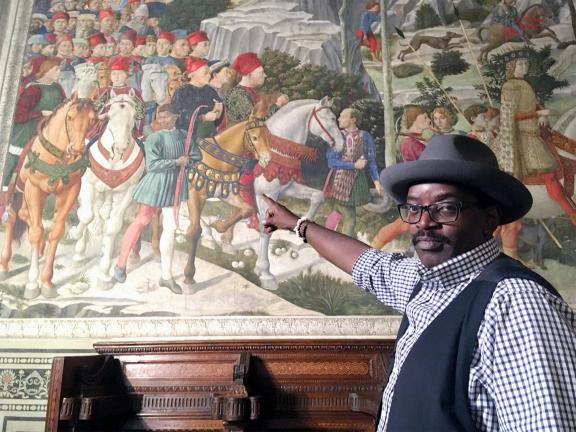 Photograph of a man wearing a hat and vest pointing at a work of art