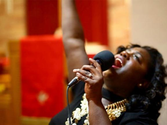 Photograph of a woman singing joyfully into a microphone