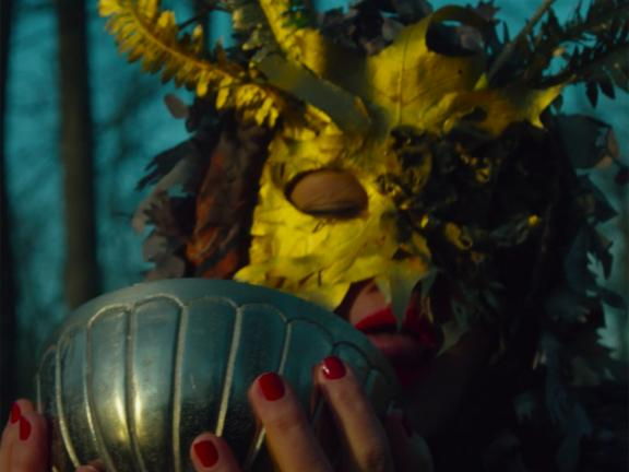 Close up photograph of a woman wearing a feathered mask and holding a bowl