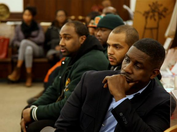 Photograph of a group of men men sitting in a courtroom with other people in the background