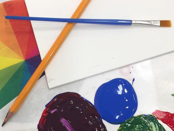 Photograph of paper, pencil, paint brush, and blobs of paint.