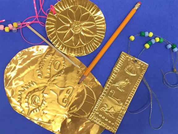 Photograph of embossing supplies, beads on a string, embossing stick, and a pencil
