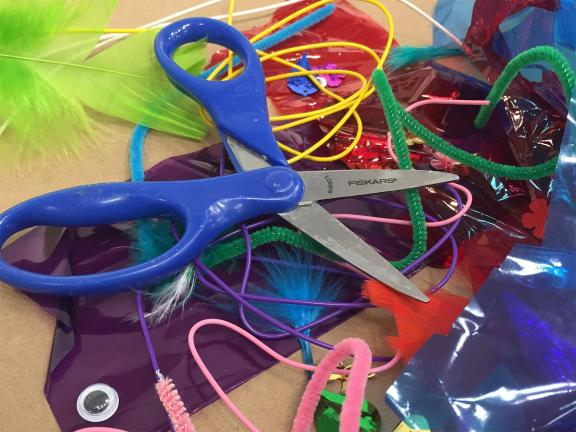 Photograph of scissors, feathers, string, cellophane, paper, pipe cleaners and art supplies on a flat surface
