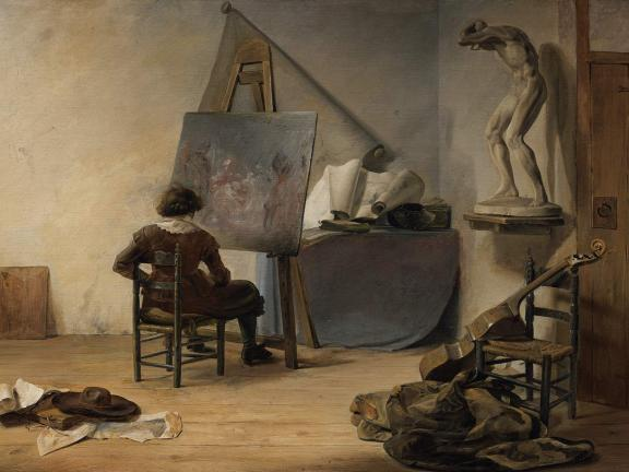A man sits in front of a half-finished canvas with his back to the viewer in a sparse but untidy studio.