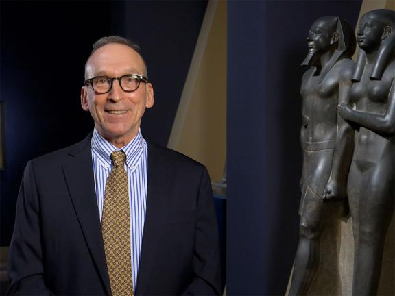 Curator Larry Berman in standing next to sculpture of King Menkaura and queen in Egyptian Sculptures gallery