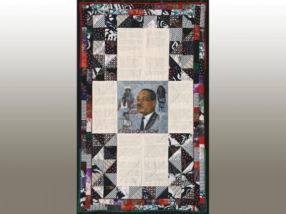 Photograph of a quilt with an image of Martin Luther King, portions of text and other people.