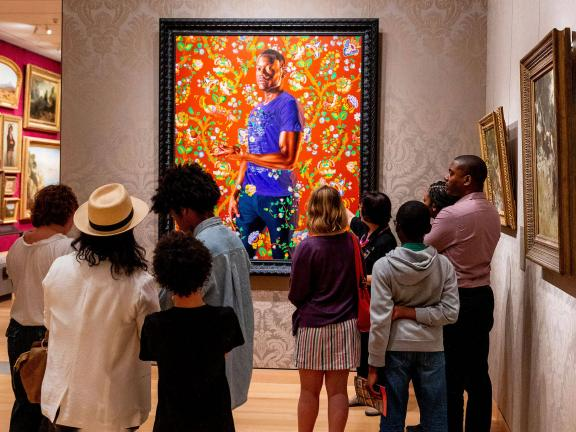 Crowd of visitors looking at painting by Kehinde Wiley, depicting young man standing amidst bright floral pattern