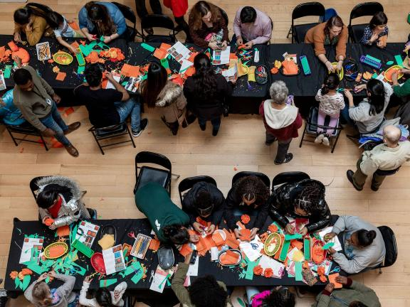 Overhead view of visitors at two long crafts tables, working with orange and green paper materials