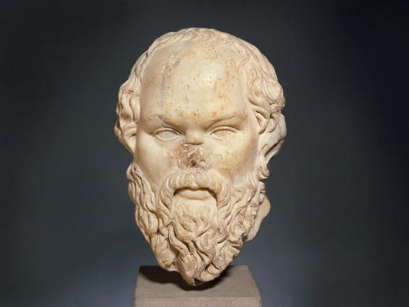 Marble bust of a man with a receding hairline, thick beard, and missing nose.
