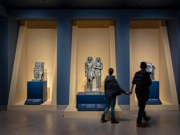 Two visitors holding hands, viewing Egyptian sculptures in gallery