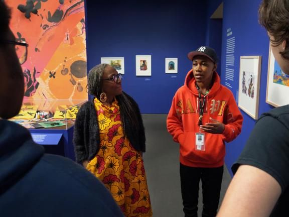 Teen speaking in front of small group, standing next to artist Ekua Holmes, in Paper Stories exhibition