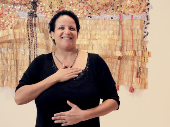 Woman signing American Sign Language in front of artwork on wall