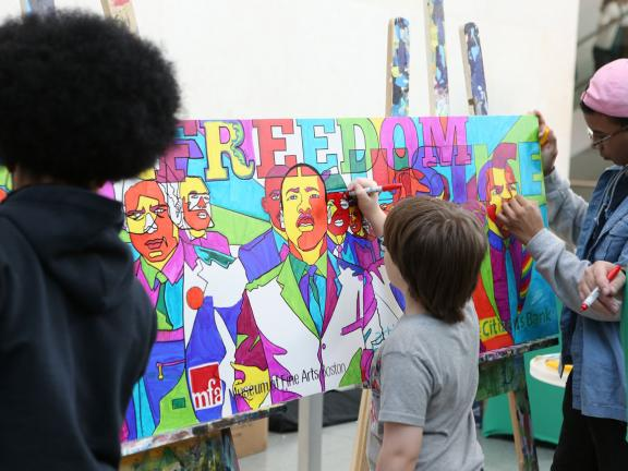 Kids coloring mural of Martin Luther King, Jr. at MLK Day celebration