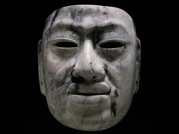 A solemn face carved out of gray and black jadeite.