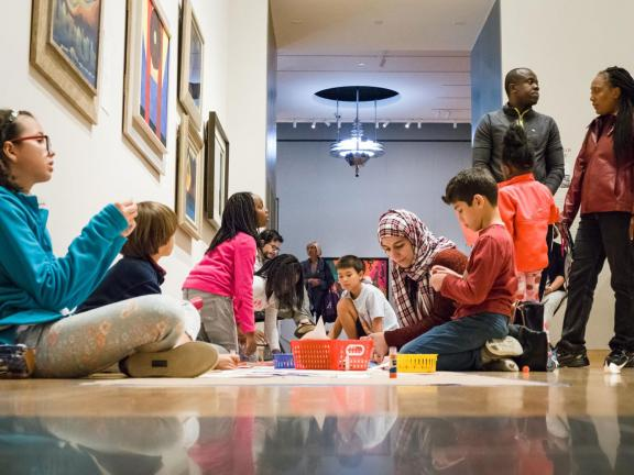 kids sitting on gallery floor working on art project