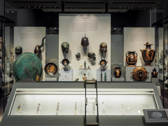 Display case filled with ancient Greek coins in foreground, with helmets and other military depictions in display case in background