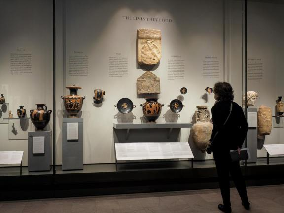 Visitor looking at display case filled with Ancient Greek pottery depicting scenes from daily life