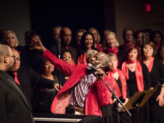Singer at microphone in bright red jacket looking back towards choir with arm reaching out