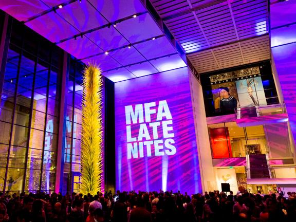 View of Shapiro Family Courtyard during MFA Late Nites, walls lit in bright purple