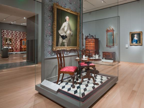 Display case with painting and chair and table set in Gallery 134