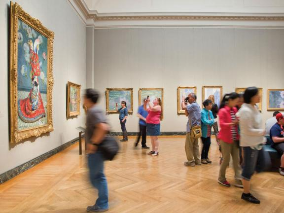 Visitors looking at French impressionist paintings in gallery