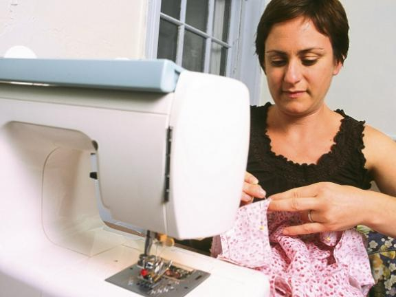 Student sews pink dress on sewing machine
