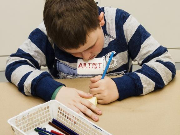 Kid in blue striped sweater drawing at table in front of box of pencils