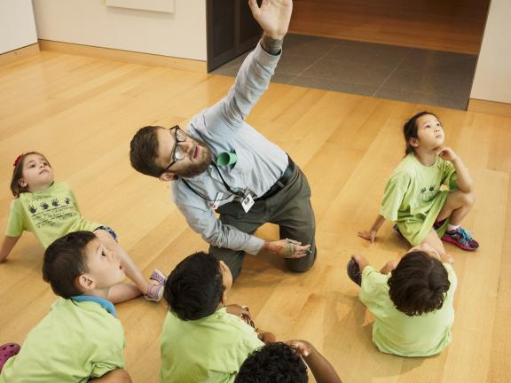 Teacher kneeling on gallery floor pointing up, with young kids in green shirts sitting around him