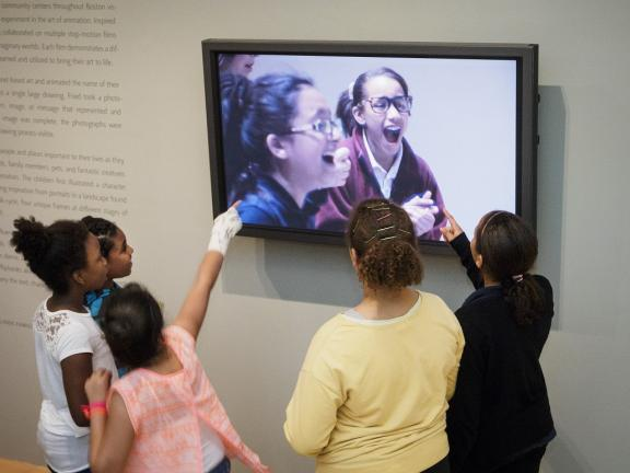 Kids pointing at screen in Community Arts Initiative installation