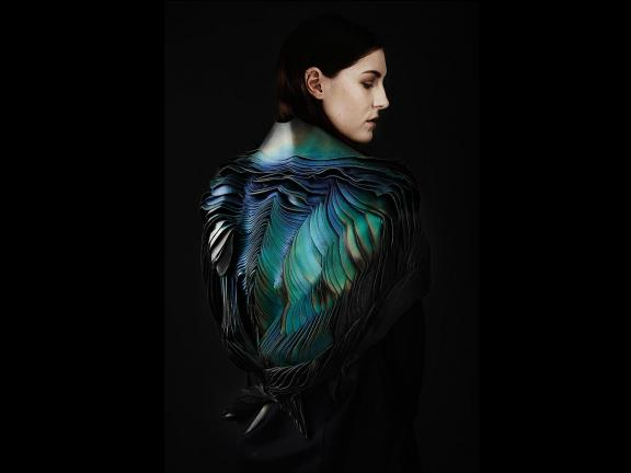 Fashion model in feathered cape
