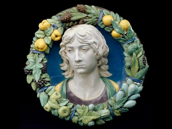 Terracotta glazed sculpture of a young man in a roundel of fruit and leaves