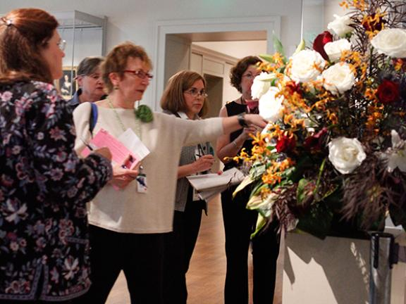 Tour guide talking about flower arrangement with groups of visitors
