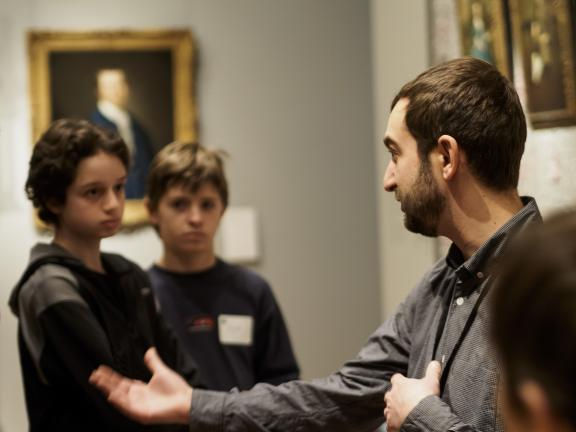 Museum staff member discusses paintings with kids at Home School event