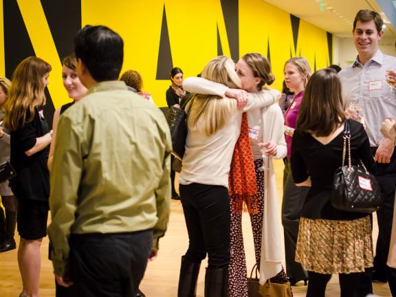 Guests mingling, hugging at Museum Council event in Linde Family Wing in front of Manana Man mural