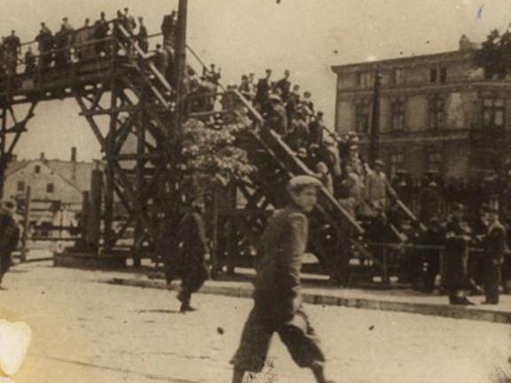 "Henryk Ross, Lodz Ghetto: Boy walking in front of the bridge crossing Zigerska (the ""Aryan"") street, 1940-44"