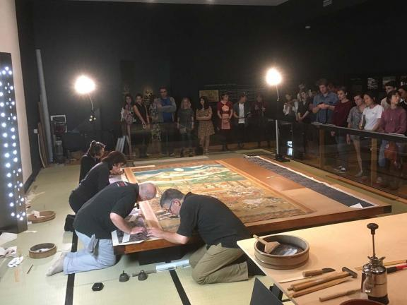 Conservators working on large scroll, The Death of the Historical Buddha, on low table in front of onlookers