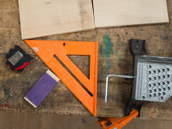 Above view of workstation with sandpaper, measuringtape, measuring triangle and wood scraps