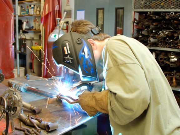 Man leans over welding project in metalwork studio