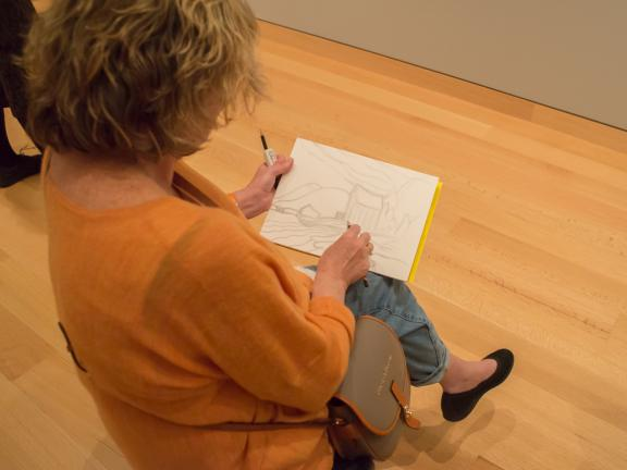 Above view of seated woman drawing landscape in gallery
