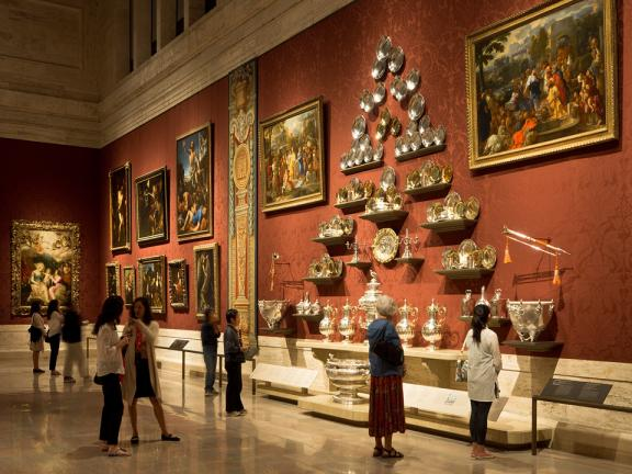 View of gallery wall with large arrangement of Hanoverian silver and various European paintings