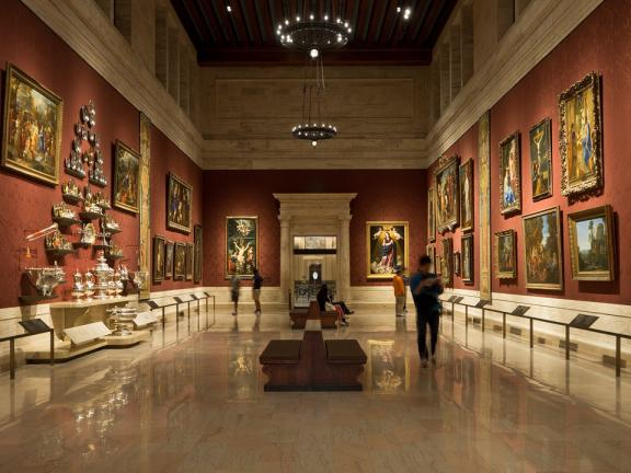 Wide view of gallery with high ceiling and reddish walled, with European paintings and silver on walls