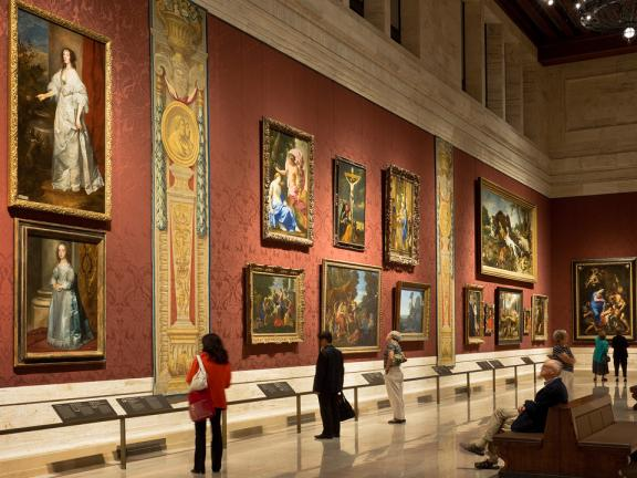 View of gallery with large European paintings and tapestries on walls