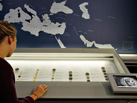 Visitor looking into display case of ancient coins