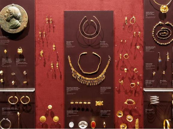 Close-up of display case filled with ancient Mediterranean jewelry