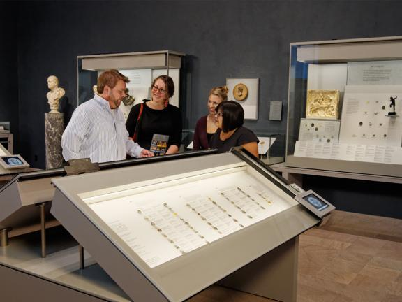 Four visitors standing behind large case of ancient coins in gallery