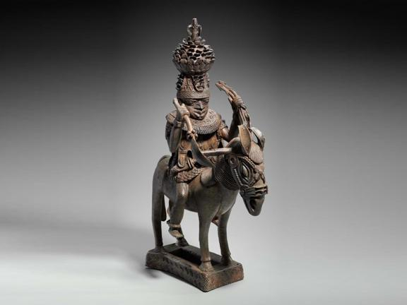 Copper sculpture of mounted man with a crown and holding the reins of a horse