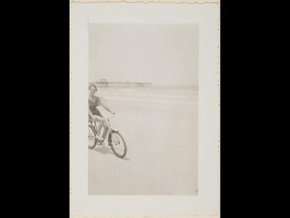 Young woman riding bicycle on beach