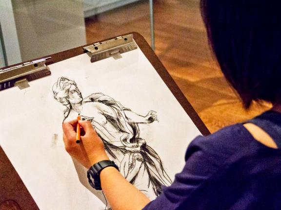 Visitor drawing statue of Juno on paper