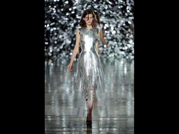 Fashion model wearing dress with silver sheen on runway